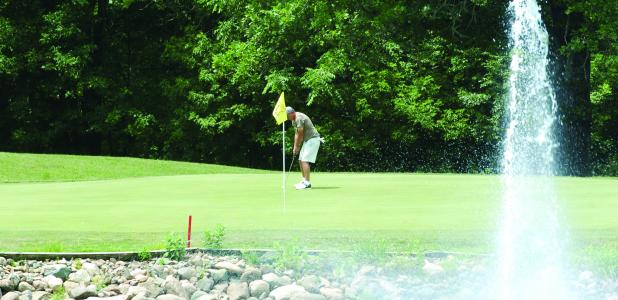 A golfer takes aim at the ball at the Dodge Country Club in Dodge Center.